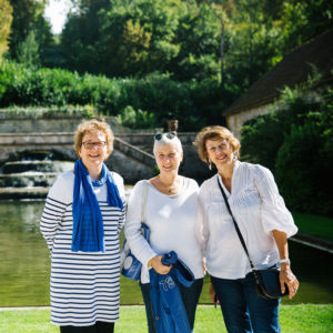 Three women standing in front of a fountain in France