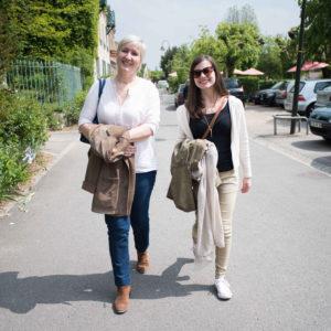 Two women walking down a sidewalk